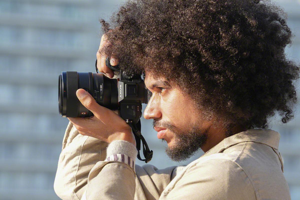 Lifestyle Bild Sony. Mann hält Kamera vor seinem Auge