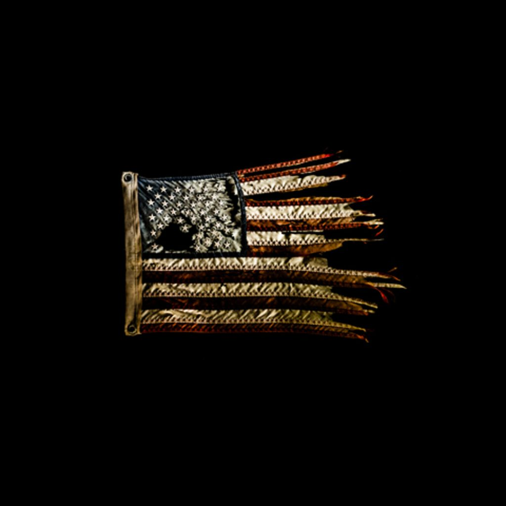Ziemlich mitgenommene und abgenutzt US-Flagge vor schwarzem Hintergrund, aufgenommen von Thomas Kretschmann