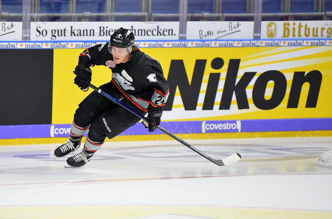 Eishockey-Spieler in Aaction vor Nikon-Banner
