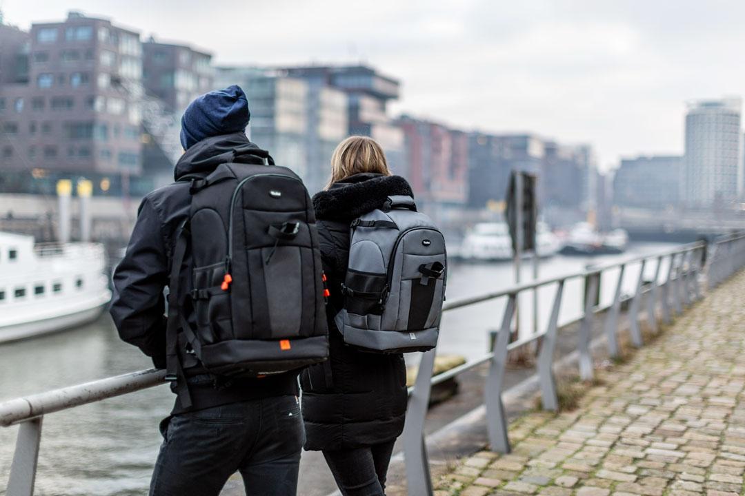 Zwei Personen am Flußufer mit Fotorucksäcken Rollei Fotoliner Ocean auf dem Rücken