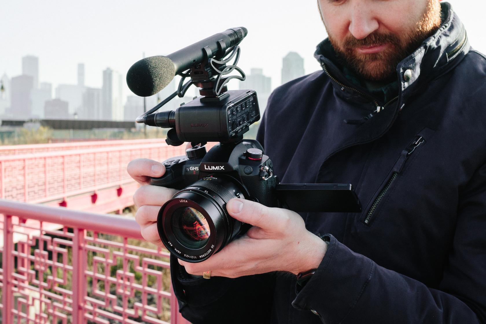 Mann auf einem Feld hält Panasonic LUMIX GH5 II mit Kikrofon-Aufsatz in der Hand