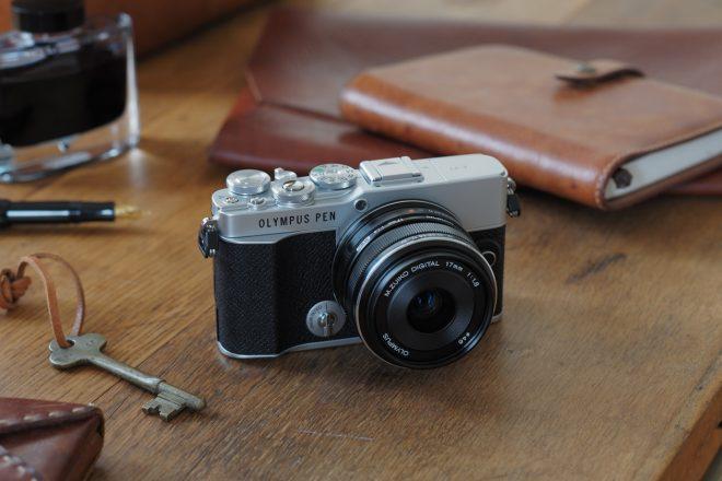 Kamera Olympus PEN E-P7 auf altem Holztisch mit Lederbuch im Hintergrund