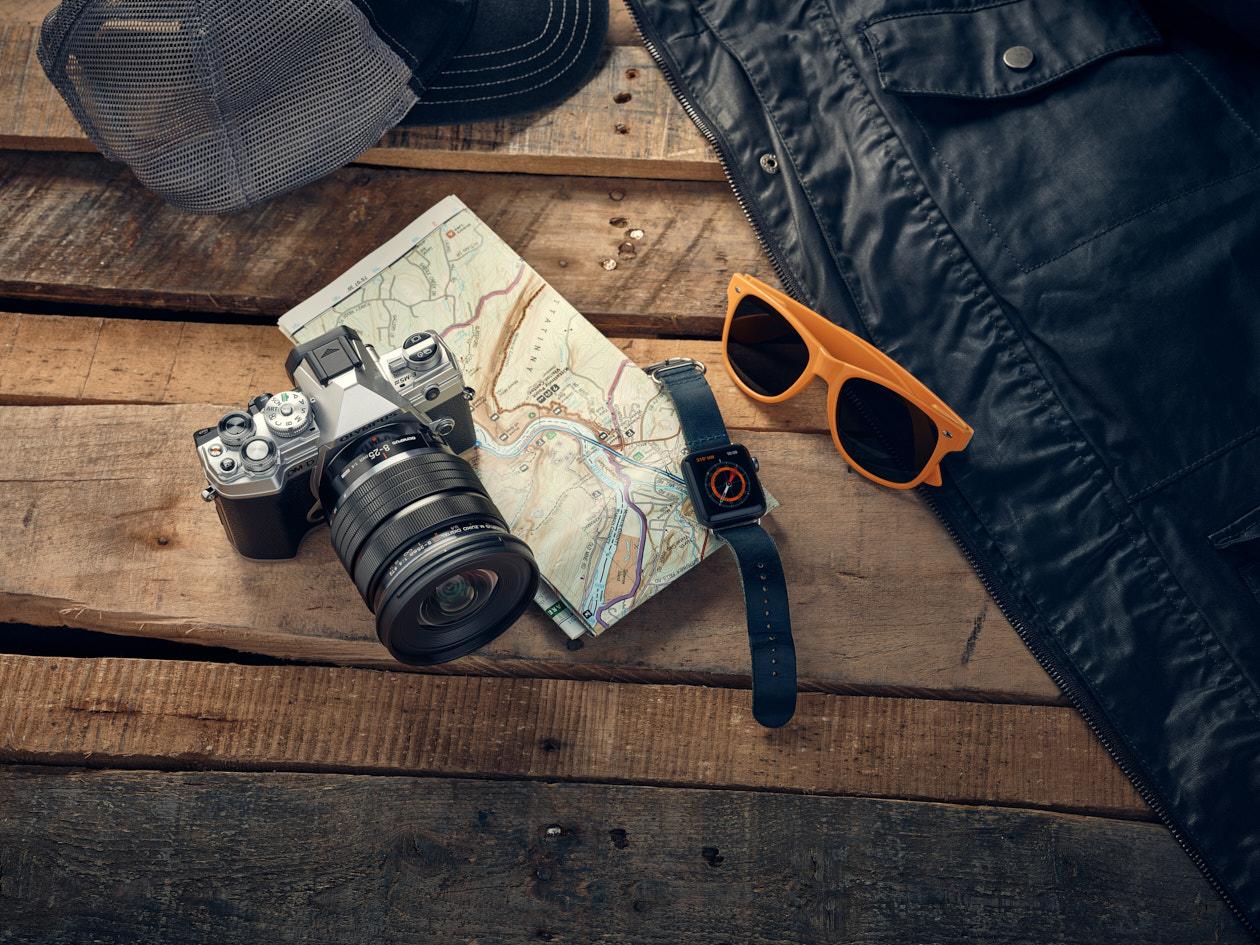 Moodbild einer Kamera mit dem Objektiv Olympus M.Zuiko Digital ED 8-25mm F4.0 PRO auf einem Holztisch mit Wanderkarte und Sonnenbrille