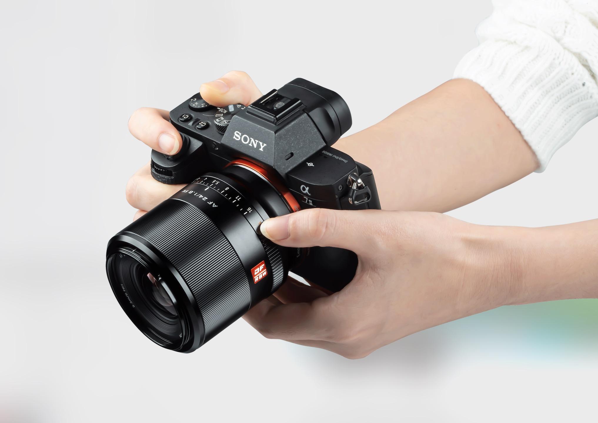 Frauenhände halten eine Sony-Kamera mit neuem 24-mm-Objektiv vor hellem Hintergrund