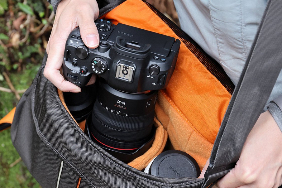 Mann holt Kamera mit dem Objektiv RF 14-35mm F4 L IS USM aus einer Kameratasche