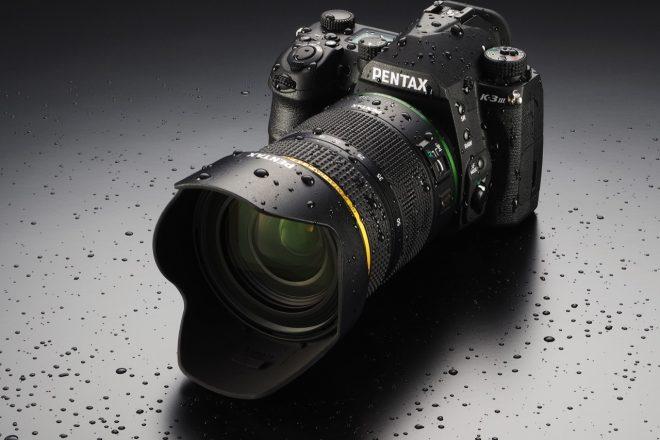 Pentax K III mit Objektiv und Wassertropfen Produktbild